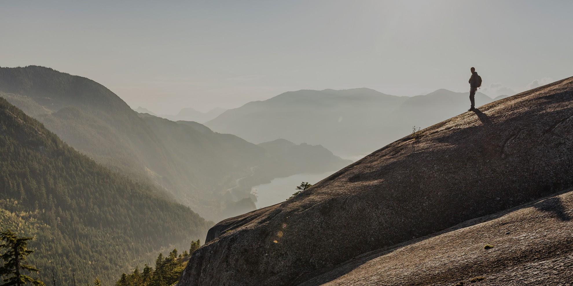 Wanderer auf Felsmassiv inmitten einsamer Berglandschaft