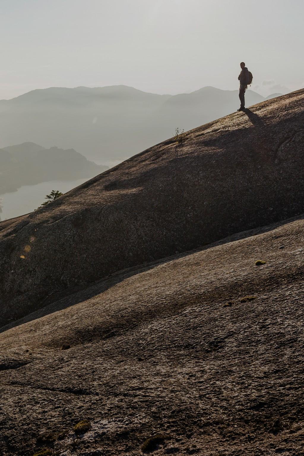 Wanderer auf Felsmassiv inmitten einsamer Berglandschaft im Portraitmodus.